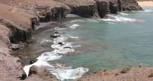 Oceano Atlântico acena na costa rochosa e na areia preta em praias de Playas Papagayo, Lanzarote vídeos de arquivo