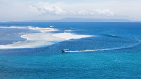 Oceano azul claro com barco e surfistas em ondas grandes Foto de Stock