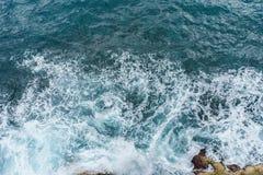 Oceano blu profondo del pericolo con l'onda che si schianta sulla costa della roccia con spr Immagini Stock