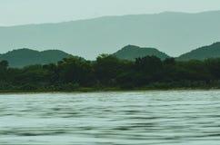Oceano com árvores e montanhas no fundo imagem de stock royalty free