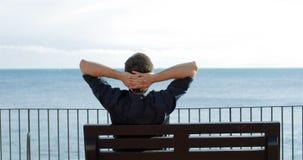 Oceano de observação de relaxamento do homem em um banco video estoque
