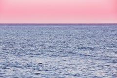Oceano del mare calmo e fondo rosa di alba di tramonto del cielo Immagini Stock