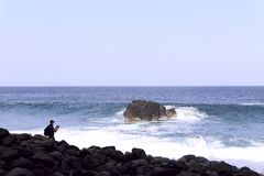 Oceano di zampillo blu con le onde e la schiuma bianca Siluetta di un uomo in una distanza immagine stock
