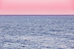 Oceano do mar calmo e fundo cor-de-rosa do nascer do sol do por do sol do céu Imagens de Stock