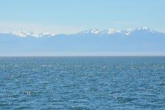Oceano e montagne blu di Snowy Fotografia Stock Libera da Diritti