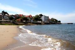 Oceano e spiaggia con le piccole case Immagini Stock