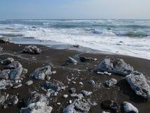 Oceano Pacífico, ondas e vistas do monte coberto de neve no inverno no tempo ensolarado em Kamchatka, Rússia imagem de stock