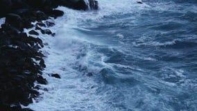 Oceano tempestoso, movimento lento delle onde che spruzzano e che si rompono sopra le pietre della scogliera archivi video