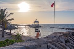 Oceanside Gazebo Sunset Beach with Lifeguard Chair. And Wind Flag in Montego Bay, Jamaica stock photo