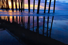 Oceanside Pier. The pier in Oceanside, California at sunset.  Scene captures pilings and relections Royalty Free Stock Image