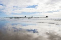 Oceanside pier with cloud reflections royalty free stock images
