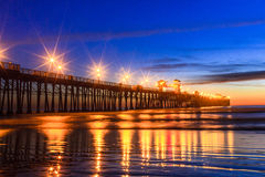 Oceanside Pier. This photograph is of the pier in Oceanside, California. The photograph was taken just after sunset. The pier lights create nice reflections in royalty free stock images