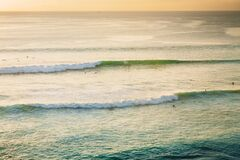 Free Oceanside With Waves And Surfers At Sunset Stock Image - 172269851
