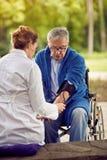 Ocena ciśnienie krwi starszych osob mężczyzna w wózku inwalidzkim Obraz Royalty Free