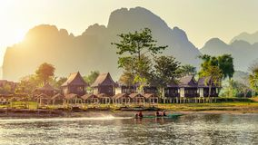 By och bungalower längs Nam Song River i Vang Vieng, Laos royaltyfri bild