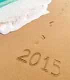 2015 och fotspår på sandstranden royaltyfria foton