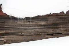 Is och istappar med snö på en mörk träbakgrund som kontrasterar vinterbakgrunden Arkivfoton