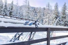 Och skidar skidar poler som lutar mot ett staket Arkivfoto