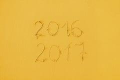 2016 och 2017 som är skriftliga på sand på stranden i gula färger royaltyfri foto
