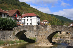 Ochagavia Bridge (Navarra, Spain). Typical houses, medieval stone bridge and river in Ochagavia, a little village in the north spanish mountains. Sunny day Royalty Free Stock Image
