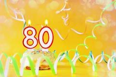 Ochenta años de cumpleaños Magdalena con las velas ardientes bajo la forma de número 80 fotografía de archivo
