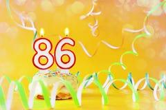 Ochenta y seis años de cumpleaños Magdalena con las velas ardientes bajo la forma de número 86 imagenes de archivo