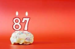 Ochenta y siete años de cumpleaños Magdalena con la vela ardiente blanca bajo la forma de número 87 imagenes de archivo
