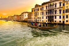 Ocho deportistas que reman una góndola del deporte en el canal de Venecia grande en la puesta del sol imagen de archivo libre de regalías