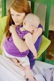 Ocho meses del bebé que duerme en manos de las madres imagenes de archivo
