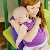 Ocho meses del bebé que duerme en manos de las madres fotografía de archivo