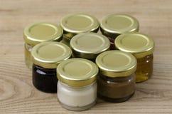 Ocho pequeños tarros de miel de los sabores de los differents Imagen de archivo