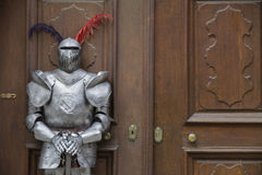 Ochraniacz - Opancerzona średniowieczna rycerz pozycja przed starym drzwi zdjęcia stock