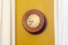 Ochre clock against wall. An old vintage clock ticking against an ochre wall with some  white curtains Royalty Free Stock Photos