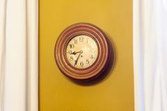 Ochre clock against wall. An old vintage clock ticking against an ochre wall with some  white curtains Royalty Free Stock Photo