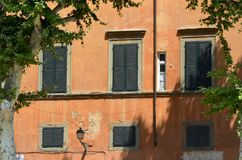 Ochre-coloured apartments in Venice, Italy. A set of apartments, covered with tradtional ochre-coloured paint, in Venice, Italy. The windows have black shutters royalty free stock photography