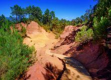 The Red Cliffs Les Ocres of Roussillon, Provence, France. The Ochre Path le Sentier des Ocres through the Red Cliffs of Roussillon Les Ocres, a nature park in stock photos