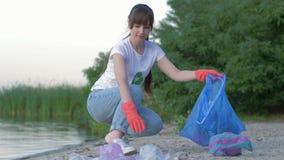 Ochrona środowiska, aktywista kobieta w gumowych rękawiczkach zbiera klingerytu i polietylenu ściółkę w torbie na śmiecie podczas zdjęcie wideo