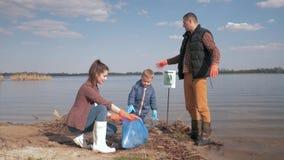 Ochrony środowiskiej, kobiety i mężczyzny wolontariuszi z dzieciak chłopiec, zbierają klingerytu i polietylenu grat na brudnym zbiory wideo