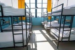 Ochtend binnen de herbergenslaapkamer met schone witte bedden voor studenten en eenzame jonge toeristen Royalty-vrije Stock Foto