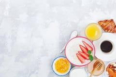 Ochtend continentaal ontbijt met hierboven koffie, croissant, havermeel, jam, honing en sap op steenlijst van Vlak leg stock afbeelding