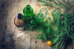 Ochtend na de viering van het Nieuwjaar Verscheidene lege flessen alcohol, spar vertakt zich, glazen op vuil stock foto