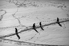 Mensen die op de sneeuwsleep lopen Stock Afbeeldingen