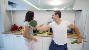 Ochtend thuis het gelukkige jonge paar onlangs wed het dansen luisteren aan muziek in keuken die pyjama's dragen Langzame Motie stock video