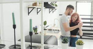 Ochtend thuis het gelukkige jonge paar onlangs wed het dansen luisteren aan muziek in keuken die pyjama's in liefde dragen die pr stock video