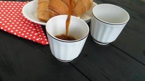 Ochtend van de koffie wordt de hete melk gegoten in kop van ontbijtcroissant stock footage