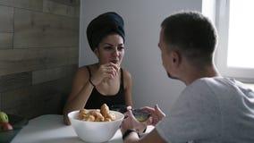 Ochtend van het gelukkige mooie jonge het paar glimlachen, het spreken en het drinken koffie met croissants tijdens ontbijt stock footage