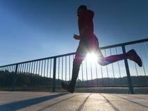 Ochtendagent in lange zwarte beenkappen die op brug uitoefenen Het openlucht uitoefenen op brug royalty-vrije stock fotografie