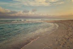 Ochtendbranding, wolken en voetafdrukken bij het strand royalty-vrije stock foto