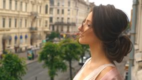 Ochtendbruid, een jonge vrouw in een roze zijderobe die zich op het balkon bevinden en voor het huwelijk voorbereidingen treffen stock footage