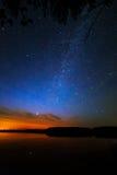 Ochtenddageraad op een sterrige hemel als achtergrond die in het water wordt weerspiegeld Royalty-vrije Stock Afbeeldingen